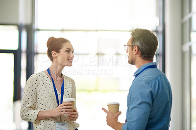 Buy stock photo Shot of businesspeople having a conversation during a coffee break in a modern office