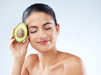Buy stock photo Studio portrait of an attractive young woman holding an avocado against a gray background