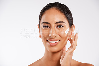 Buy stock photo Studio portrait of a beautiful young woman applying lotion while posing against a gray background