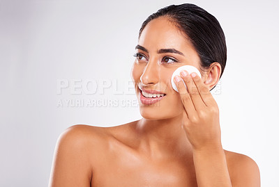 Buy stock photo Studio shot of a beautiful young woman applying lotion while posing against a gray background