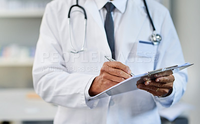 Buy stock photo Closeup shot of an unrecognizable pharmacist using a clipboard in a chemist