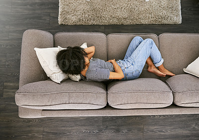 Buy stock photo High angle shot of a young woman experiencing stomach pain on the sofa at home