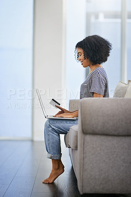 Buy stock photo Shot of an attractive young woman using a laptop and credit card on the sofa at home