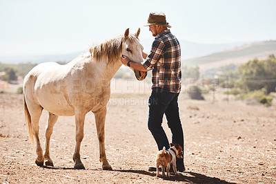 Buy stock photo Shot of a farmer standing with a horse on a ranch