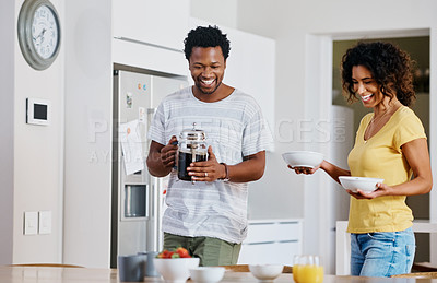 Buy stock photo Cropped shot of a young married couple about to have breakfast together in the kitchen at home