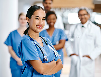 Buy stock photo Portrait of a nurse standing in a hospital with her colleagues in the background