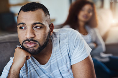 Buy stock photo Cropped shot of a young man looking upset after having an argument with his girlfriend