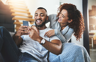 Buy stock photo Cropped shot of a handsome young man and his girlfriend looking at something on his cellphone while relaxing on the sofa at home