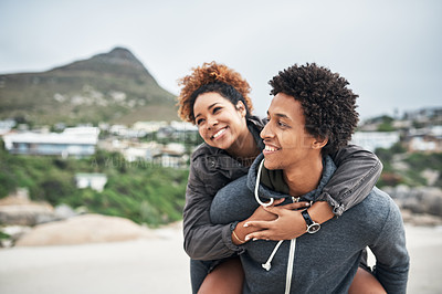 Buy stock photo Cropped shot of a happy young man giving his girlfriend a piggyback ride