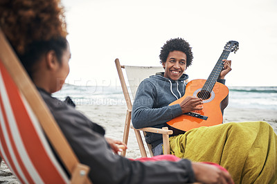 Buy stock photo Shot of a young man playing the guitar for his girlfriend at the beach