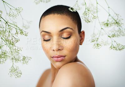 Buy stock photo Studio shot of a beautiful young woman posing amongst delicate flowers