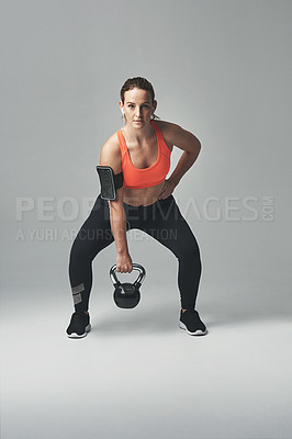 Buy stock photo Studio portrait of an athletic young woman working out with a kettle bell against a grey background