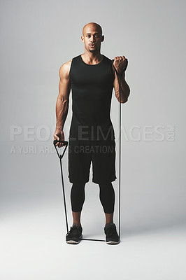 Buy stock photo Studio portrait of an athletic young man working out with a resistance band against a grey background