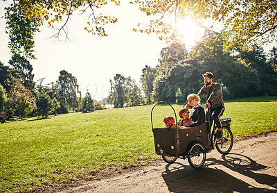 Buy stock photo Full length shot of a young man taking his family around the park on a cargo bike