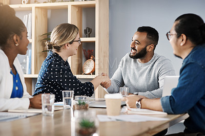 Buy stock photo Shot of a young businessman and businesswoman shaking hands during a meeting with colleagues in a modern office