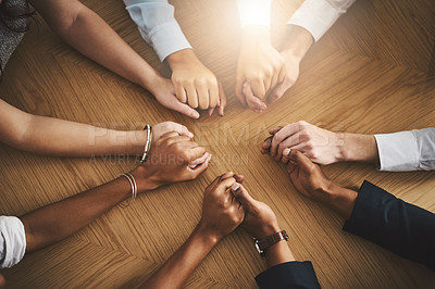 Buy stock photo Closeup shot of a group of businesspeople sitting together at a table and holding hands