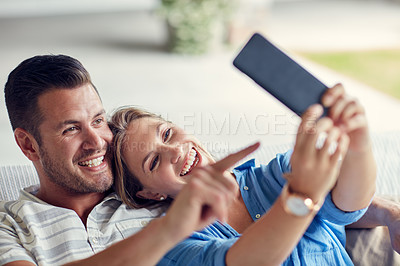 Buy stock photo Cropped shot of a young married couple taking a selfie using a cellphone on the sofa at home