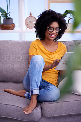 Buy stock photo Shot of an attractive young woman using a digital tablet while relaxing on the sofa at home