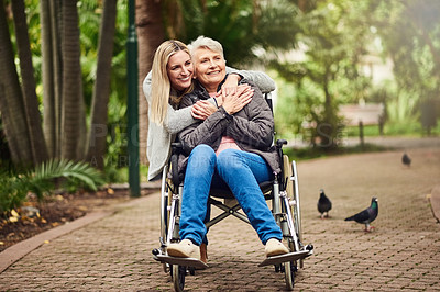 Buy stock photo Shot of a senior woman in a wheelchair spending time outdoors with her daughter