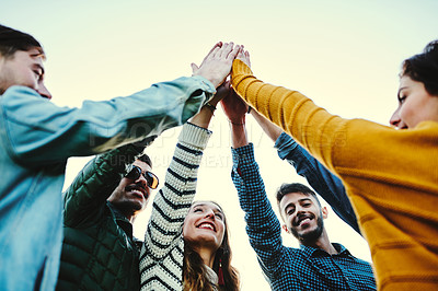 Buy stock photo Cropped shot of friends hands huddled together giving each other a high five outdoors