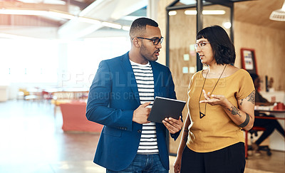 Buy stock photo Shot of two designers working on a digital tablet together in an office