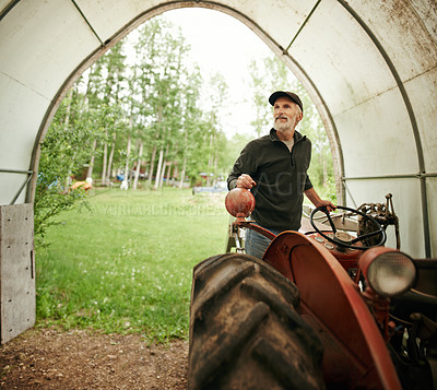 Buy stock photo Shot of a man operating a tractor on a farm