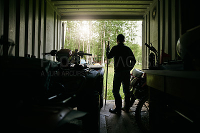 Buy stock photo Shot of a mature man standing in the shed of a farm