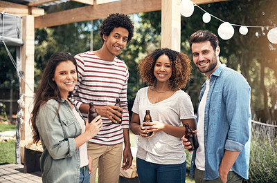 Buy stock photo Portrait of a group of friends drinking beer together outdoors