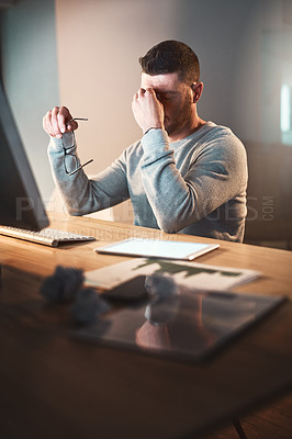Buy stock photo Shot of a mature businessman looking stressed out while working late in an office