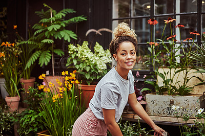 Buy stock photo Cropped shot of an attractive young woman standing in front of her flower shop