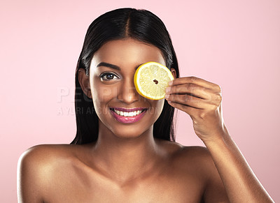 Buy stock photo Studio portrait of a beautiful young woman posing with an orange slice against a pink background