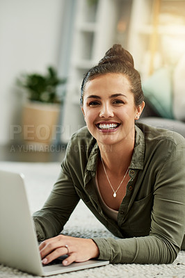 Buy stock photo Cropped shot of a beautiful young woman using a laptop while chilling on the floor in her new home