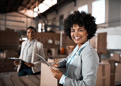 Buy stock photo Portrait of a factory manager using a digital tablet in a warehouse with her colleague in the background