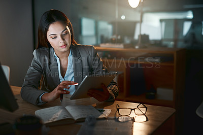 Buy stock photo Shot of a young businesswoman writing notes while using a digital tablet in an office at night