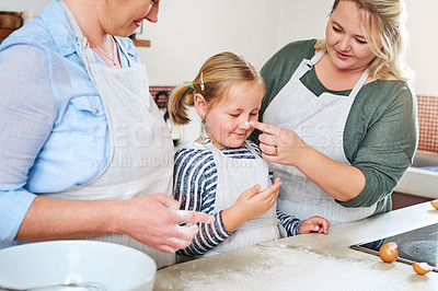 Buy stock photo Shot of an adorable little girl baking with her mother's at home