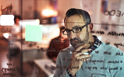 Buy stock photo Cropped shot of a handsome mature businessman looking thoughtful while working on a glass wipe board in his office