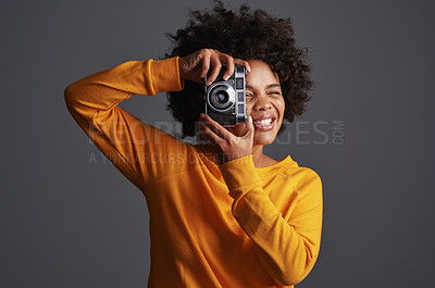 Buy stock photo Shot of a young woman taking pictures on a vintage camera against a grey background