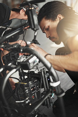 Buy stock photo Behind the scenes shot of a videographer working on a state of the art video camera inside of a studio during the day