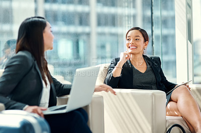 Buy stock photo Shot of two young businesswomen having a discussion in the waiting room on a business trip