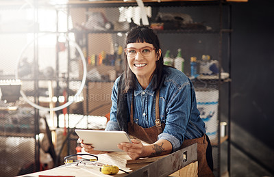Buy stock photo Cropped portrait of an attractive young woman working on her laptop while standing in her creative workshop