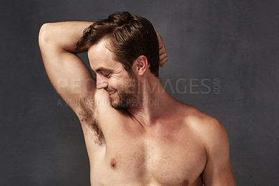 Buy stock photo Cropped shot of a handsome young man smelling his armpits