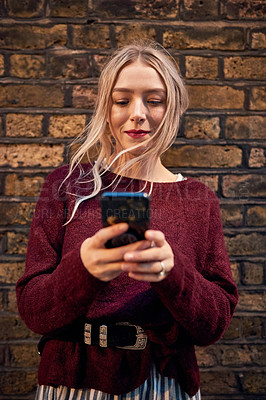 Buy stock photo Shot of a young woman using a smartphone against a brick wall in the city