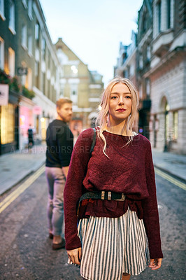 Buy stock photo Shot of a young man and woman walking past each other in a city street