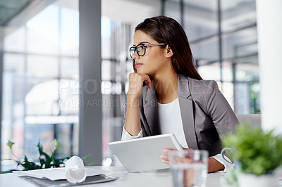 Buy stock photo Cropped shot of a young businesswoman looking thoughtful while working in an office