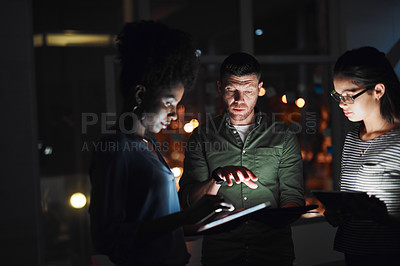 Buy stock photo Shot of a group of businesspeople working together on a digital tablet in an office at night