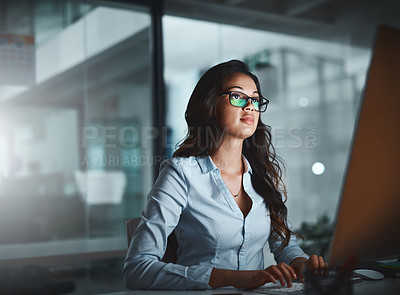 Buy stock photo Shot of a young businesswoman using a computer while working late in a modern office