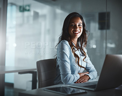 Buy stock photo Shot of a young businesswoman using a laptop while working late in a modern office