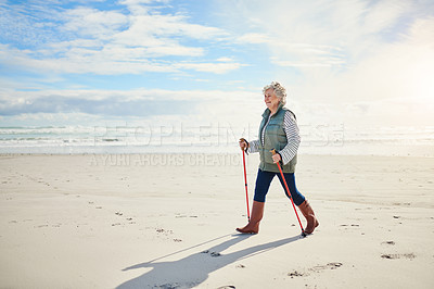 Buy stock photo Shot of a senior woman going for a walk along the beach
