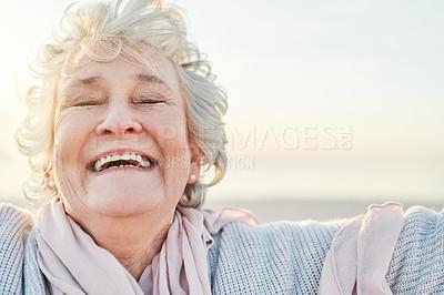 Buy stock photo Shot of a senior woman enjoying a day at the beach