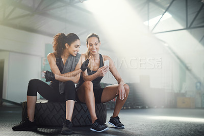 Buy stock photo Shot of two sporty young women looking at something on a cellphone while sitting at the gym